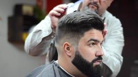 Barbiere che fa taglio di capelli d'avanguardia facendo uso del pettine al negozio di barbiere stock footage