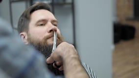 Barbiere che fa taglio di capelli del ` s della barba con gli uomini adulti con una barba lunga nel salone di capelli del ` s deg archivi video