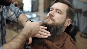 Barbiere che fa taglio di capelli del ` s della barba con gli uomini adulti con una barba lunga nel salone di capelli del ` s deg stock footage