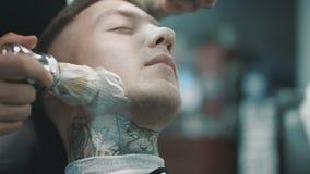 Barbiere che mette una certa crema da barba su un cliente archivi video