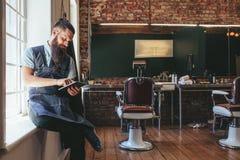 Barbiere che organizza il suo affare facendo uso della compressa digitale fotografia stock libera da diritti