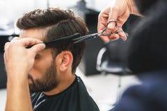 Barbiere che per mezzo delle forbici e del pettine fotografia stock libera da diritti