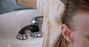 Barbiere che pulisce la testa del suo cliente con un asciugamano archivi video