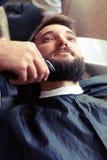 barbiere che rade barba con il rasoio elettrico fotografia stock