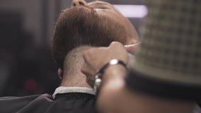 barbiere che rade barba con il rasoio elettrico Chiuda su della barba maschio della guarnizione del barbiere archivi video