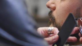 Barbiere che rade fine barbuta dei pantaloni a vita bassa su archivi video