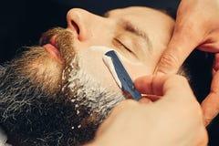 Barbiere che rade maschio barbuto con un rasoio tagliente fotografia stock libera da diritti