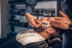 Barbiere che rade maschio barbuto con un rasoio tagliente fotografie stock