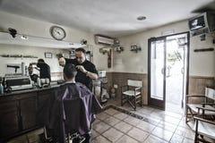 Barbiere che si rade con un rasoio al giovane in un negozio del barbiere fotografia stock