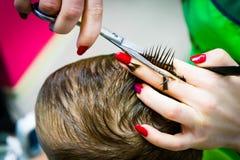 Barbiere che taglia le forbici di un bambino Foto del primo piano immagini stock