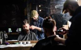 Barbiere con i capelli della guarnizione del tagliatore sulla nuca del cliente Concetto dell'acconciatura dei pantaloni a vita ba immagine stock