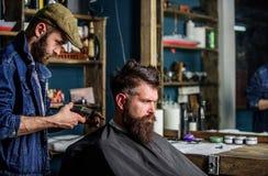 Barbiere con i capelli della guarnizione del tagliatore sulla nuca del cliente Cliente dei pantaloni a vita bassa che ottiene tag fotografia stock