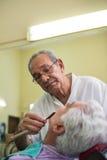 Barbiere con il rasoio che rade cliente nel negozio di barbiere fotografia stock libera da diritti