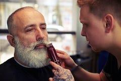 Barbiere con il tatuaggio che fa taglio di capelli all'uomo senior dei pantaloni a vita bassa immagine stock libera da diritti