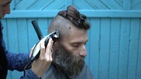Barbiere della donna che rende a pantaloni a vita bassa taglio di capelli maschio con il rasoio elettrico ed il pettine dei capel video d archivio