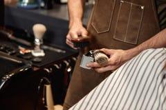 Barbiere ed uomo barbuto nel negozio di barbiere fotografia stock