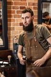 Barbiere ed uomo barbuto nel negozio di barbiere immagine stock