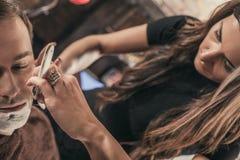 Barbiere femminile che rade un cliente fotografie stock libere da diritti