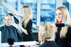 Barbiere femminile con hairdryer che fa taglio di capelli maschio fotografia stock