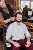 barbiere giovane che pettina capelli del cliente fotografia stock libera da diritti