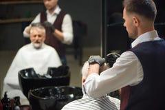 Barbiere in guanti neri che governa e che disegna taglio di capelli del cliente immagine stock