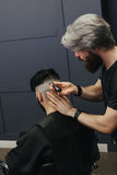Barbiere maschio che pettina e che rade capelli di un cliente maschio Fotografia Stock Libera da Diritti