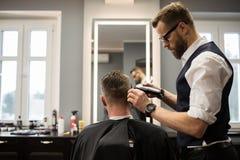 Barbiere messo a fuoco che ha capelli del cliente fotografie stock