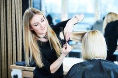 Barbiere o stilista sul lavoro Capelli della donna di taglio del parrucchiere immagini stock libere da diritti