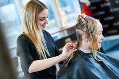 Barbiere o stilista sul lavoro Capelli della donna di taglio del parrucchiere fotografia stock