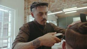 Barbiere professionista che dà un taglio di capelli d'avanguardia al cliente video d archivio