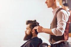 Barbiere professionista che disegna capelli del suo cliente immagine stock