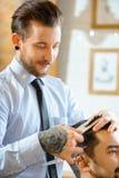 Barbiere professionista che fa taglio di capelli immagini stock