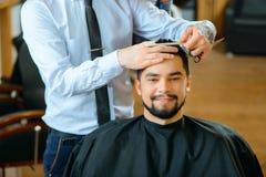 Barbiere professionista che fa taglio di capelli fotografie stock