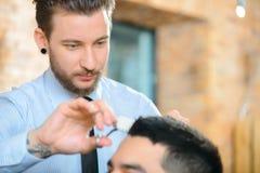Barbiere professionista che fa taglio di capelli fotografia stock libera da diritti