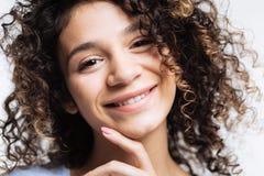 Barbilla conmovedora y sonrisa de la mujer rizada alegre Imagen de archivo