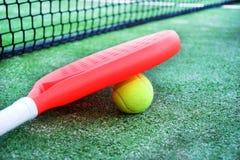 Barbotez la raquette et la boule de tennis dans le domaine de tennis de palette Images stock