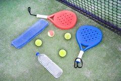 Barbotez la raquette et la boule de tennis dans le domaine de tennis de palette Image stock