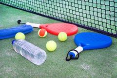 Barbotez la raquette et la boule de tennis dans le domaine de tennis de palette Photographie stock libre de droits