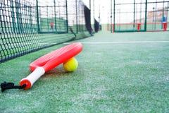 Barbotez la raquette et la boule de tennis dans le domaine de tennis de palette Photographie stock