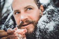 Barbuto nordico affamato mangia la carne Uomo barbuto nordico del superstite con un pezzo di carne Fotografia Stock