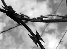Barbwire Close Up. Shows a closeup of barbed wire in front of cloudy sky Royalty Free Stock Photos