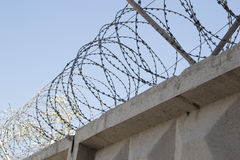 The barbwire. Concrete fence with a barbed wire against the sky Stock Image