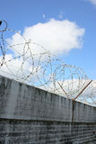 Barbwire and grey wall on sky background Royalty Free Stock Photo