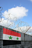 Barbwire and grey wall with Syria flag Royalty Free Stock Photo