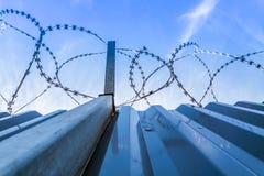 Barbwire ochrony ogrodzenie z niebieskim niebem Zdjęcia Royalty Free