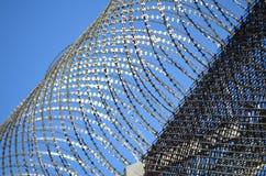 Barbwire op een gevangenismuur Stock Foto's