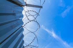 Barbwire protection fence with blue sky Stock Images