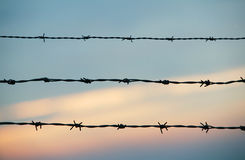 Barbwire and sky.JH. Old rusty barbwire with sunset in the background.JH stock image