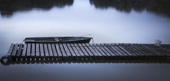 Barca abbandonata sul lago al molo Immagine Stock
