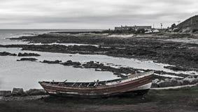 Barca abbandonata sulla linea costiera brulla Fotografia Stock Libera da Diritti